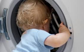 Baby climbing into washing machine.