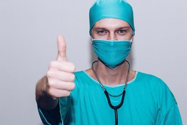 Doctor in scrubs giving a 'thumbs up'