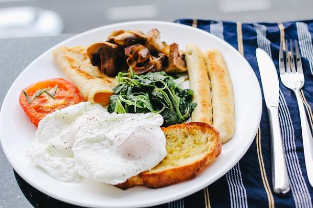 A cooked breakfast with various items including spinach, egg and tomato.