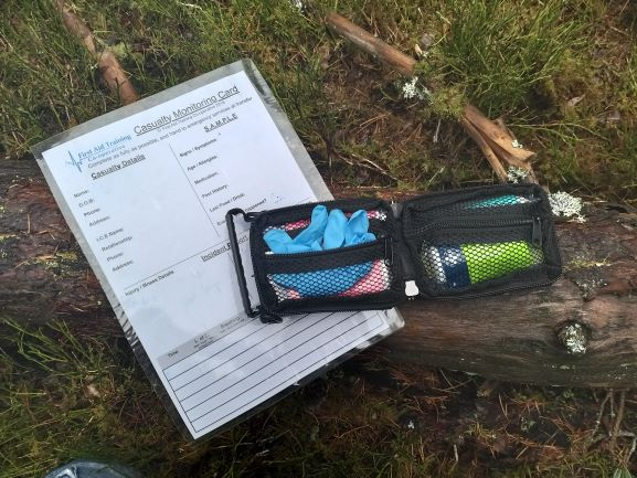 A first aid kit and casualty monitoring card in a woodland setting.