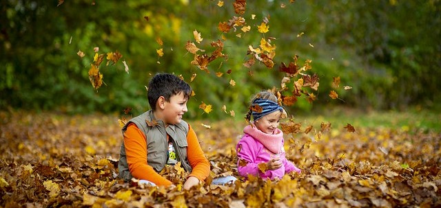 A boy and a girl playing in falling autumn leaves