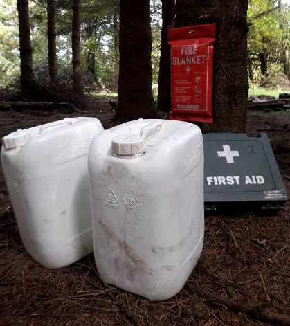 Some water bottles, a fire blanket and first aid kit in a woodland setting.