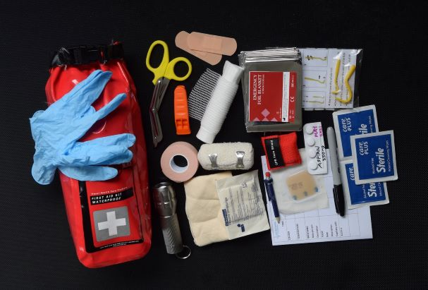 An outdoor first aid kit with all components in view including scissors, bandages, record cards and a waterproof cary case.