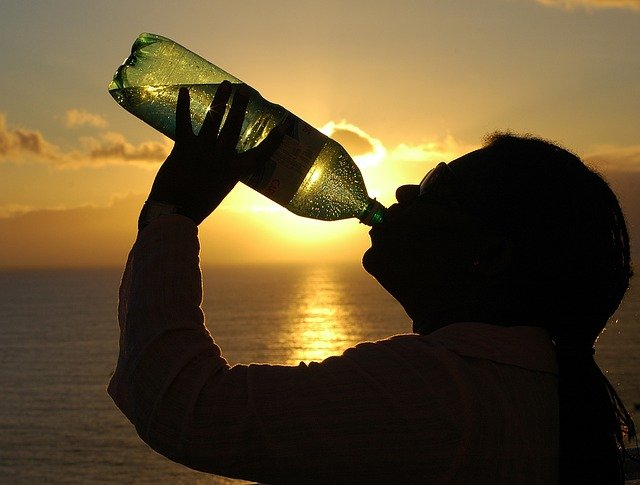 A person drinking from a large water bottle with a sunset in the background.
