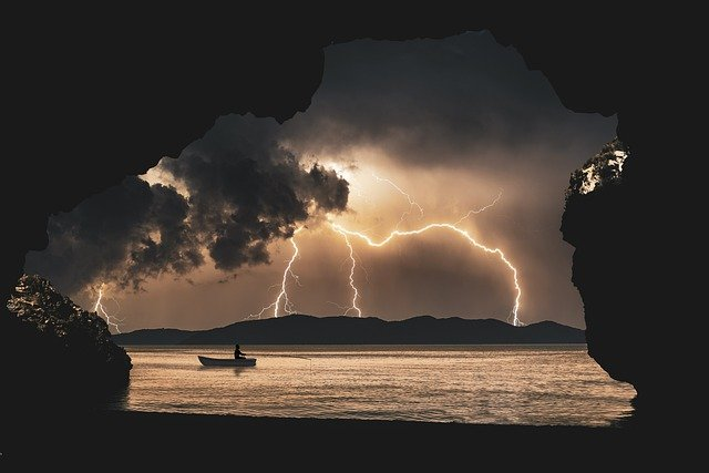 view of lightning and kayaker on a loch