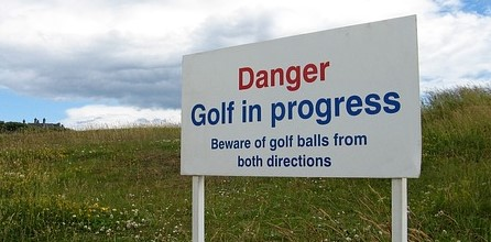 """A sign saying """"Danger: Golf in progress. Beware of balls from both directions"""""""